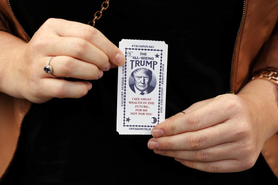 """A woman holds a ticket dispensed from a Donald Trump themed fortune telling machine. The machine tells people that they """"look poor"""" and that they should let a """"rich puppet tell their future"""". When a button is pushed it prints out a card with a """"misfortune"""". REUTERS/Lucas Jackson"""